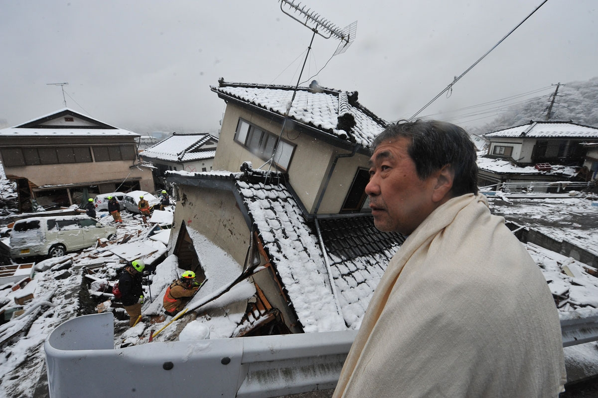A man looks on as US rescue workers search for survivors in a house in Kamaishi, Iwate prefecture on March 16, 2011, after the devasting earthquake and ensuing tsunami on March 11. T