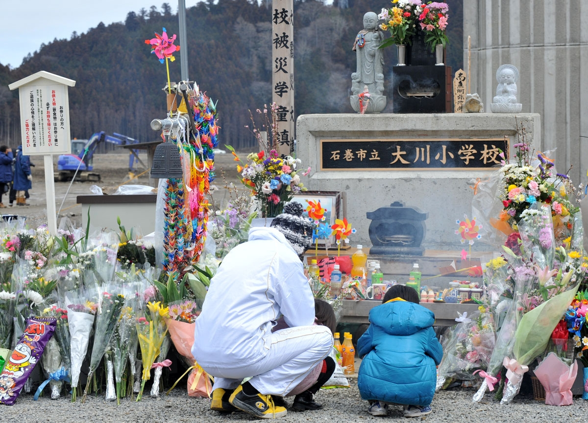 A family pray for 74 elementary school children and 10 teachers who lost their lives in the March 11 earthquake and tsunami, at a memorial in front of the Okawa elementary school during the first year anniversary of the disaster in Ishinomaki, Miyagi pref