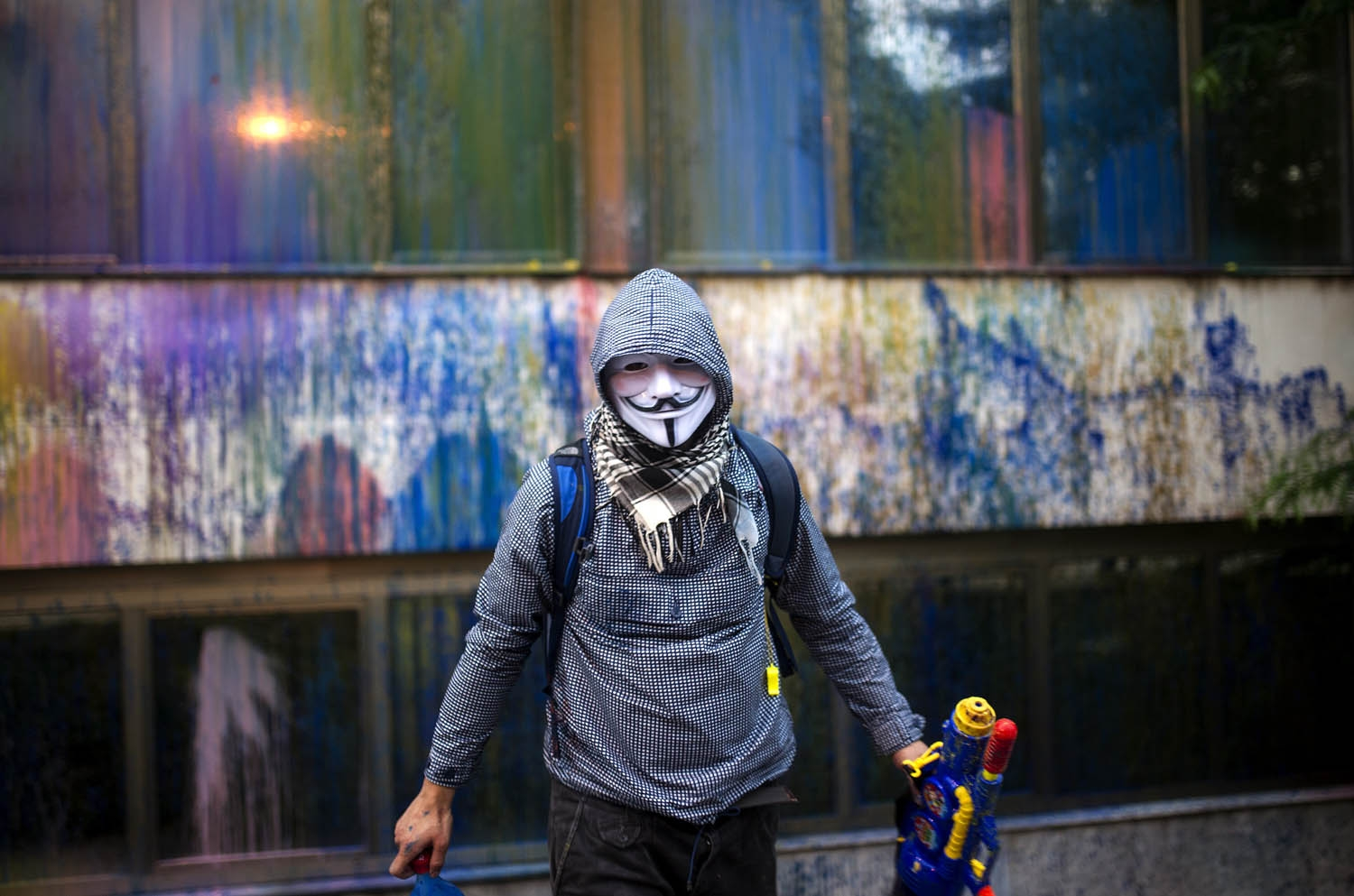 A protester wearing a Guy Fawkes mask, sprays paint with toy water gun on the facade of the Macedonia's Public Revenue Office headquarters on May 10, 2016 in Skopje