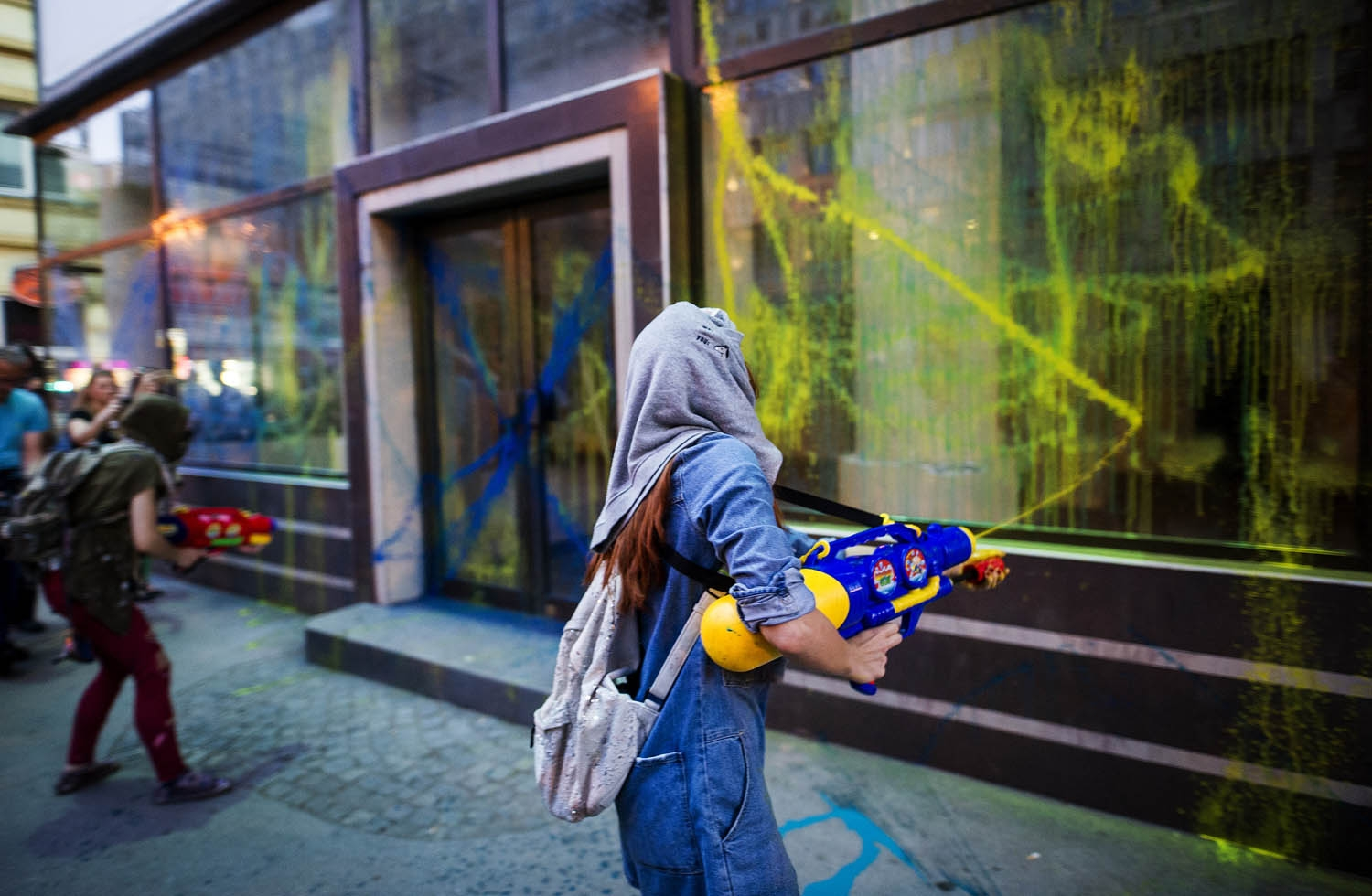 Protestors wearing masks use water guns to spray coloured paint on the public office of President Gjorge Ivanov during an anti-government protest in Skopje on May 31, 2016,