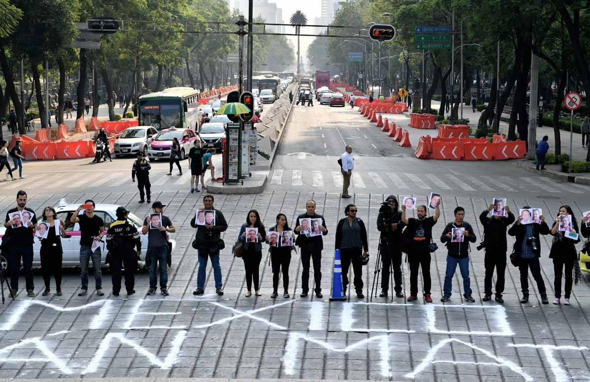 Journalists hold pictures of journalists recently murdered in different Mexican states during a protest by journalistsat at the Independence Angel square in Mexico City on May 16, 2017.