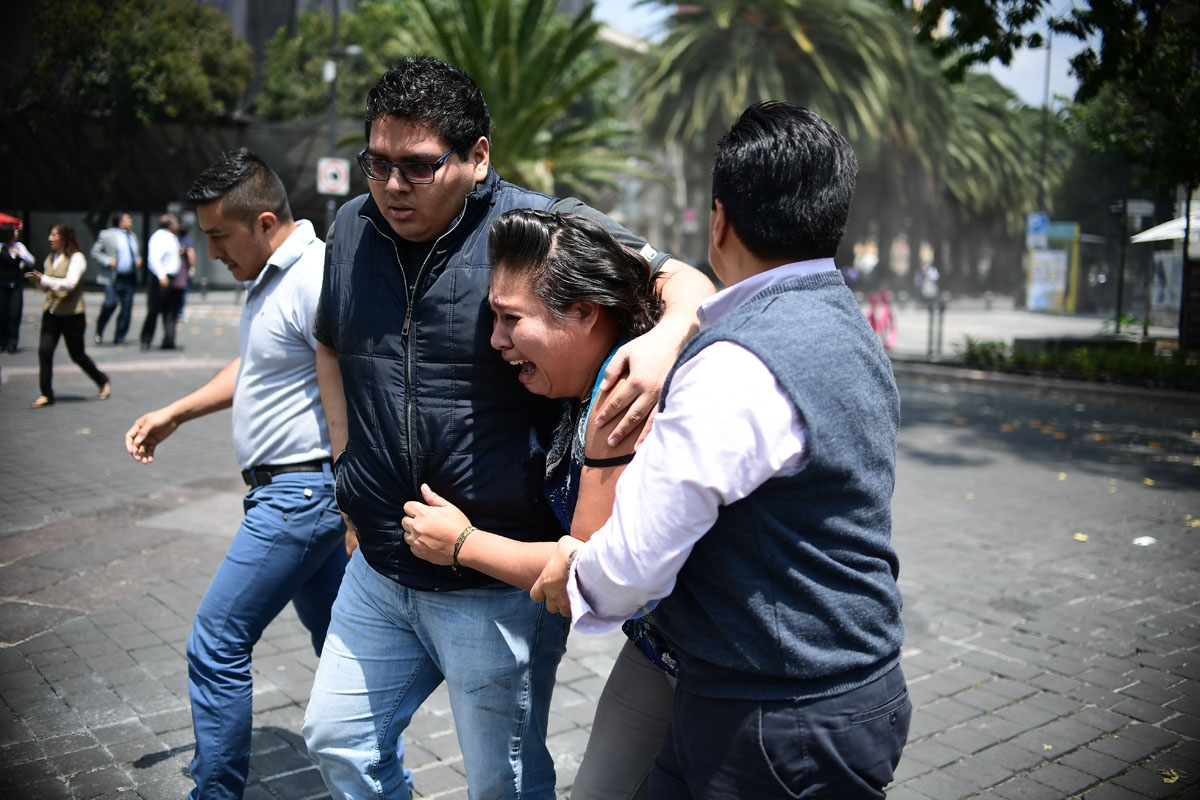 People react as a real quake rattles Mexico City on September 19, 2017 moments after an earthquake drill was held in the capital.