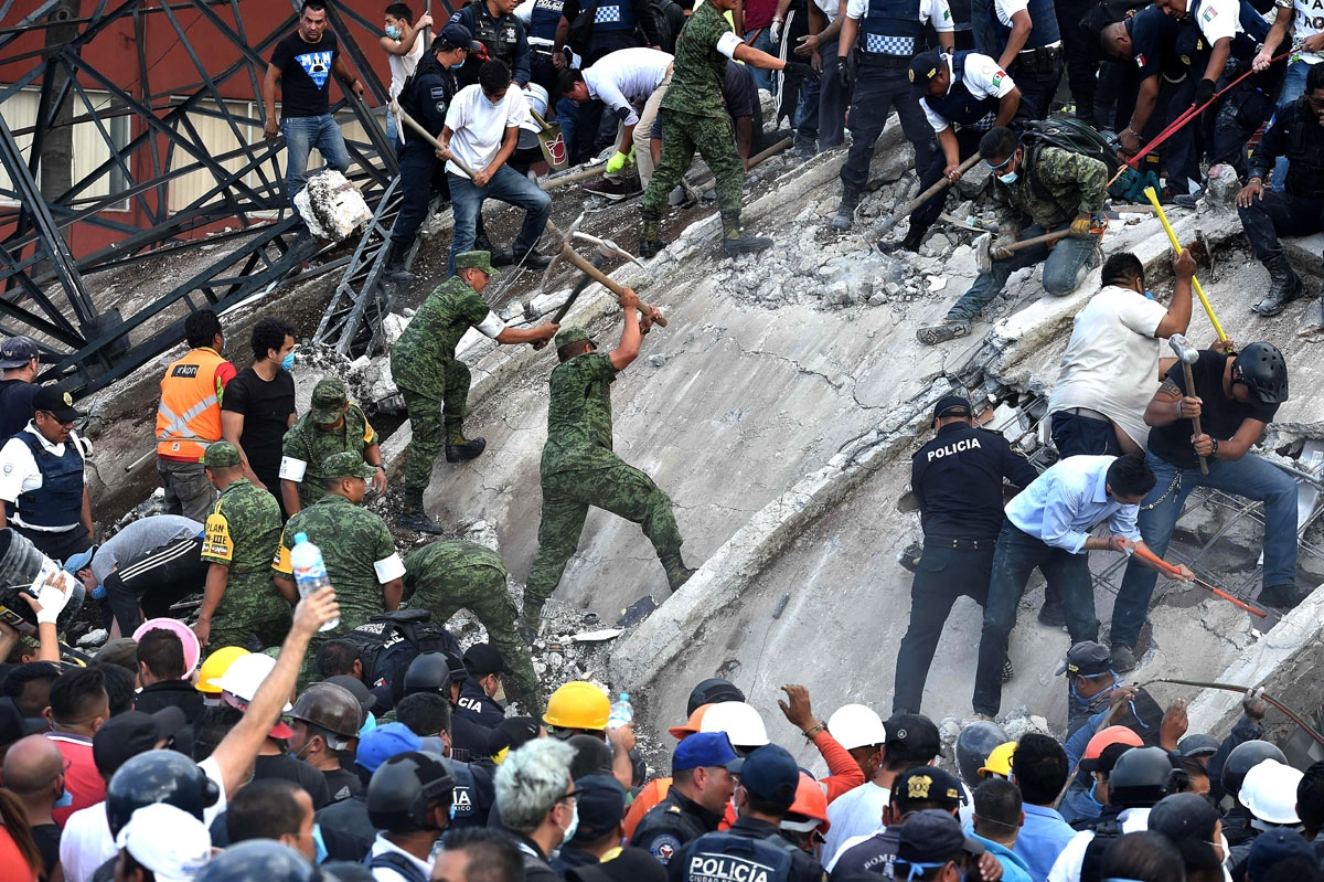 Rescuers, firefighters, policemen, soldiers and volunteers remove rubble and debris from a flattened building in search of survivors after a powerful quake in Mexico City on September 19, 2017.