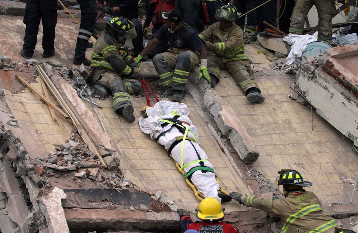 Rescuers and firefighters lower the corpse from a house that was destroyed after a powerful quake in Mexico City on September 20, 2017.