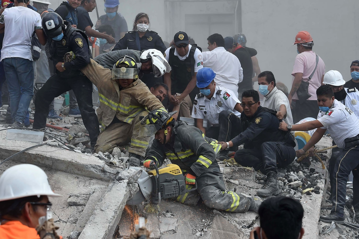 Rescuers, firefighters, policemen, soldiers and volunteers desperately remove rubble and debris from a flattened building in search of survivors after a powerful quake in Mexico City on September 19, 2017.