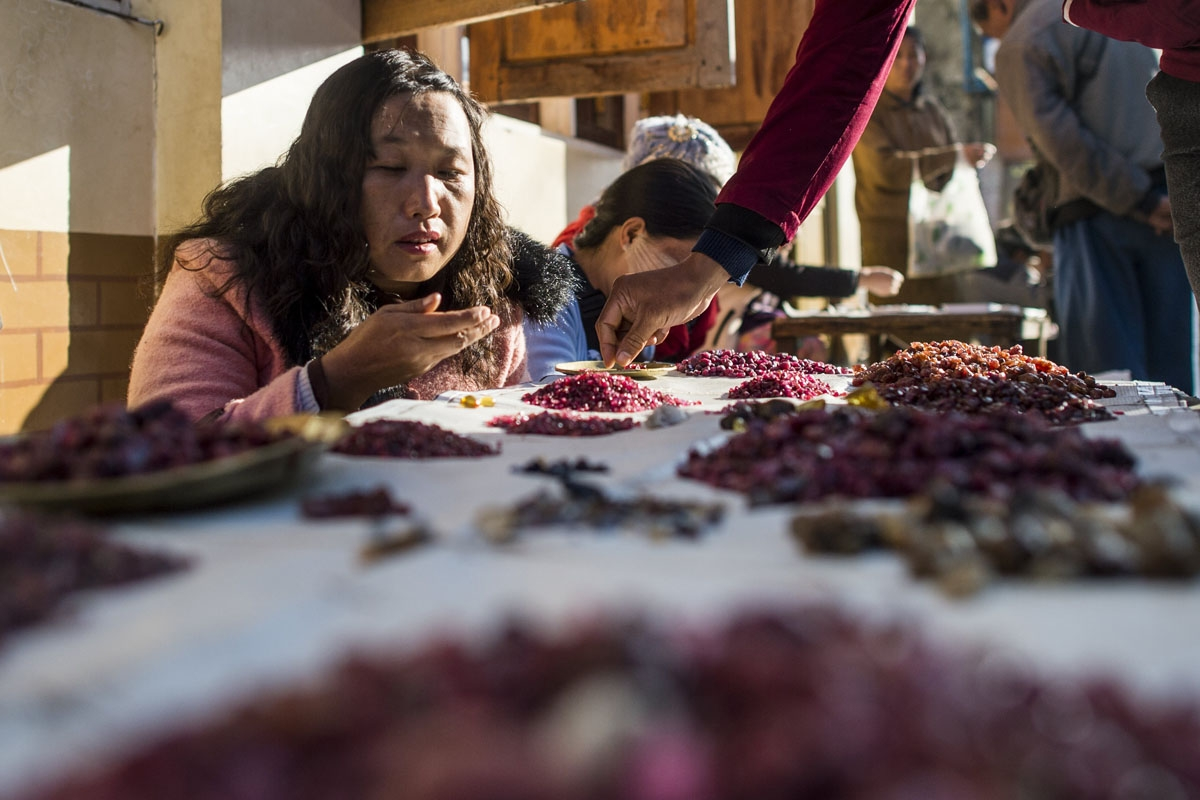 This photo taken on November 25, 2016 shows a buyer looking at rubies in the gems market in Mogok, north of Mandalay.