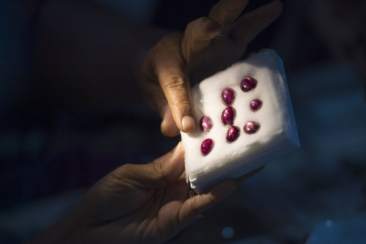 This photo taken on November 22, 2016 shows a buyer looking at rubies in a jade market in Mandalay.