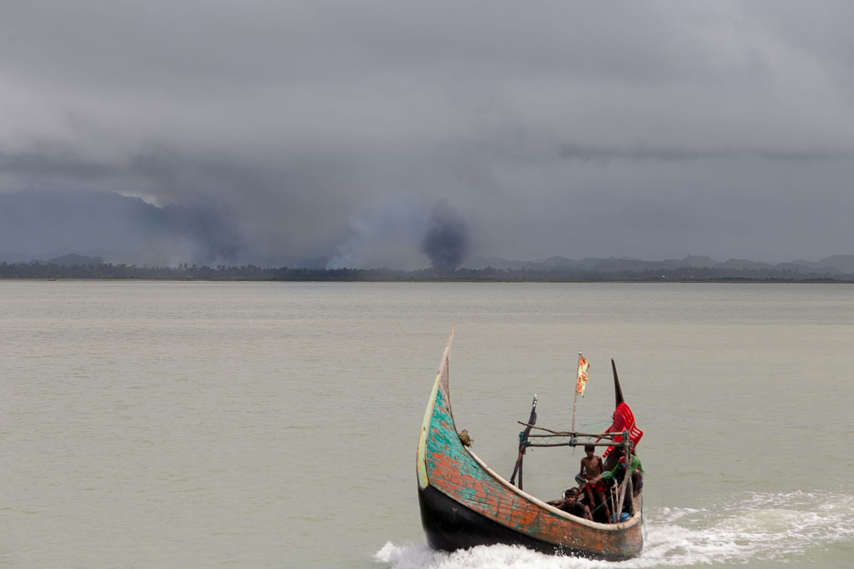 This photograph taken on September 12, 2017 shows Rohingya refugees arriving by boat, as smoke rises from fires on the shoreline behind them, at Shah Parir Dwip on the Bangladesh side of the Naf River after fleeing violence in Myanmar.