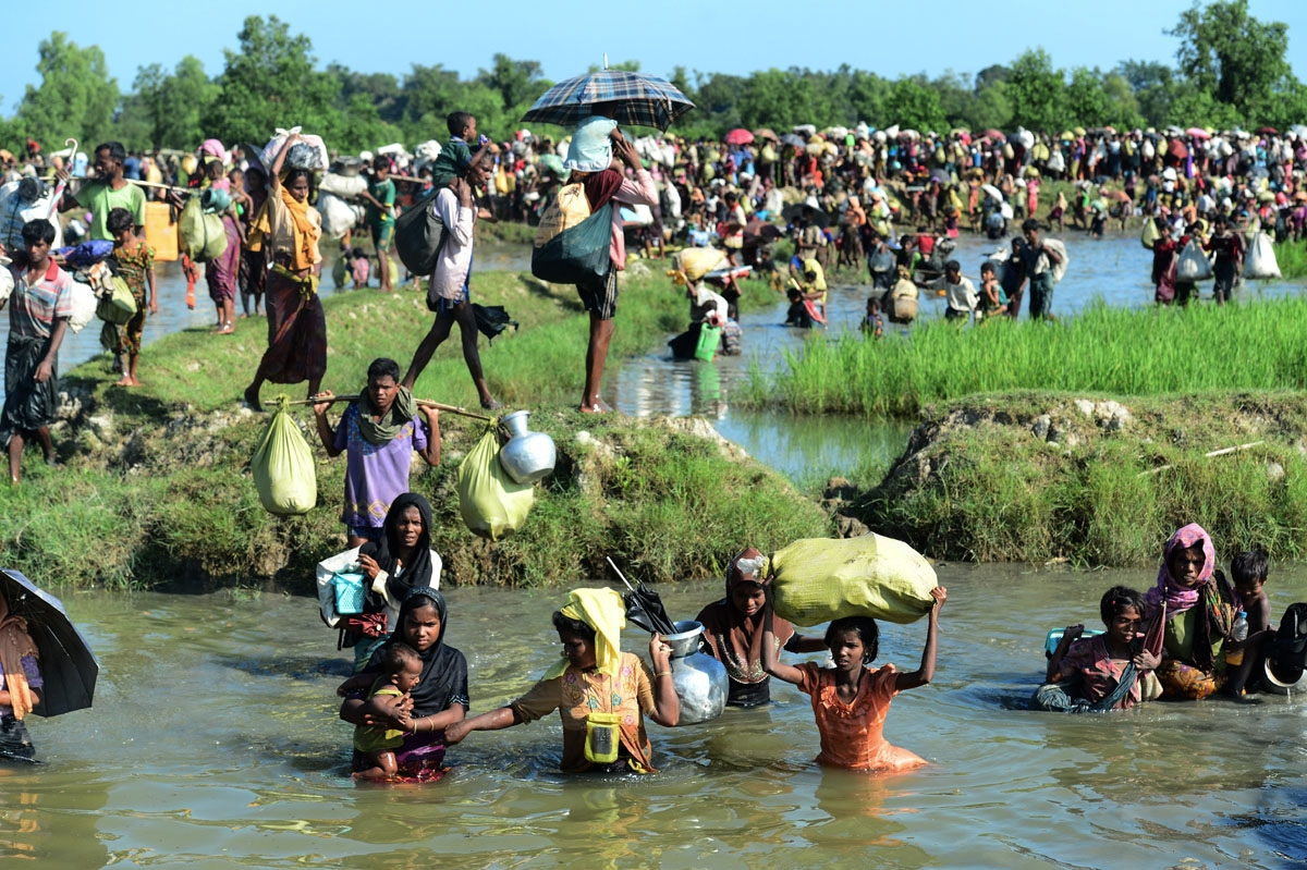 Rohingya refugees walk through a shallow canal after crossing the Naf River as they flee violence in Myanmar to reach Bangladesh in Palongkhali near Ukhia on October 16, 2017.