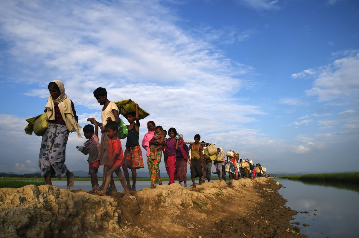 Rohingya Muslim refugees who were stranded after leaving Myanmar walk towards the Balukhali refugee camp after crossing the border in Bangladesh's Ukhia district on November 2, 2017.