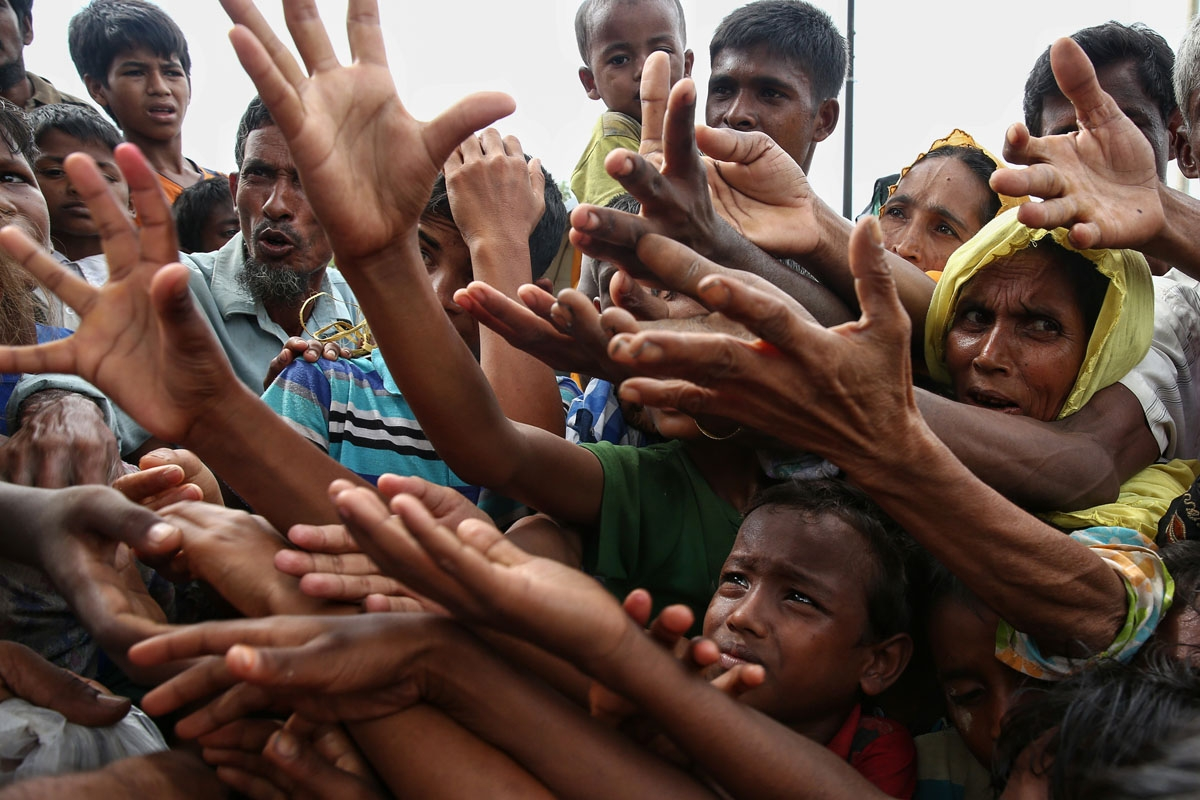 Rohingya refugees reach for food aid at the Kutupalong refugee camp in Ukhiya near the Bangladesh-Myanmar border.