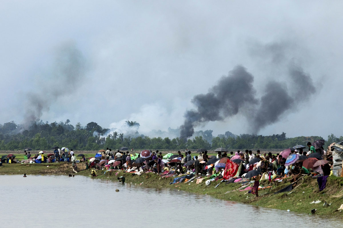 Smoke billows above what is believed to be a burning village in Myanmar's Rakhine state as members of the Rohingya Muslim minority take shelter in a no-man's land between Bangladesh and Myanmar in Ukhia on September 4, 2017.