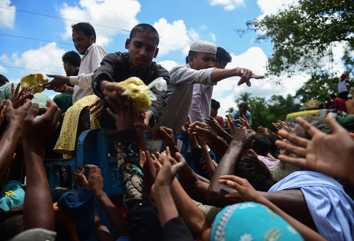 Rohingya refugees from Myanmar gather around a truck delivering food aid in Ukhia on September 14, 2017.