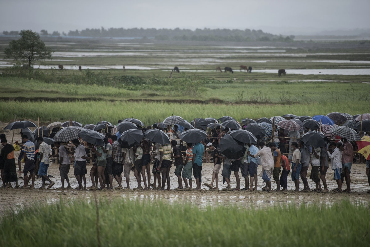 Rohingya Muslim refugees wait in line under the rain during a food distribution under at Nayapara refugee camp in Bangladesh's Ukhia district on October 6, 2017.