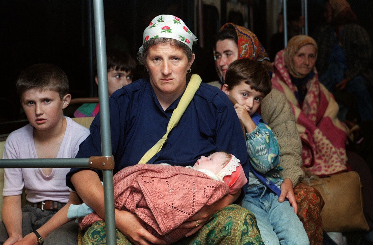 Women and children evacuees sit in a bus on July 26 1995 as they are driven by Bosnian Serbs from the fallen enclave of Zepa without UN escorts to the frontline crossing point close to the government held town of Klandanj. A UN convoy of armoured ambulanc
