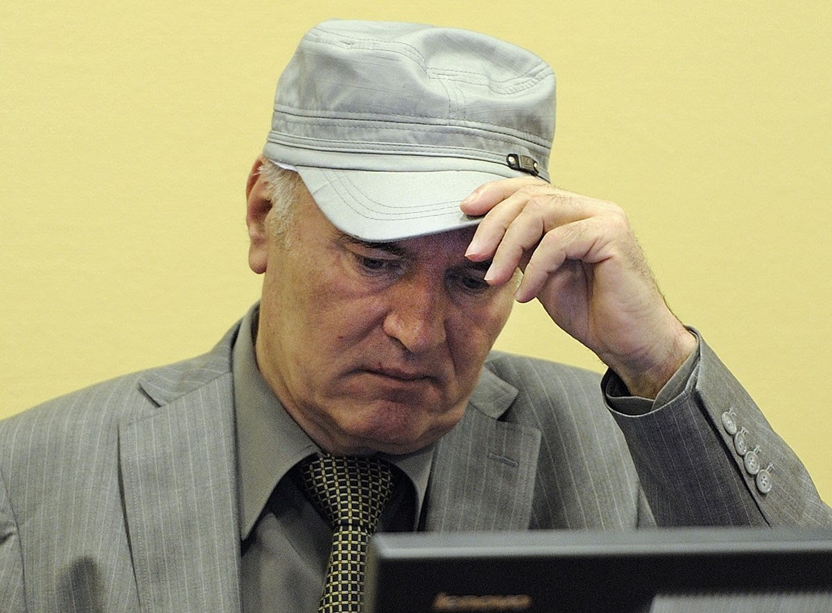 Wartime Bosnian Serb army chief Ratko Mladic adjusts his cap in the court during his initial appearance at UN war crimes tribunal in The Hague, Netherlands, on June 3, 2011