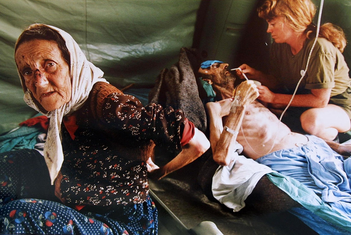 A picture taken on July 11, 1995 shows an elderly Muslim woman and her husband getting treatment for injuries inflicted on them by Serb military forces as they fled the east Bosnian enclave of Srebrenica. A