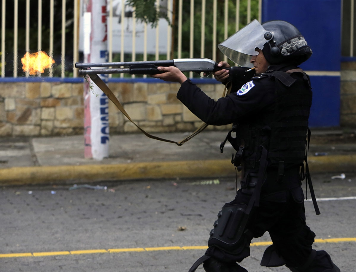 A riot police officer fires a weapon during clashes with students taking part in a protest in Managua on May 28, 2018.
