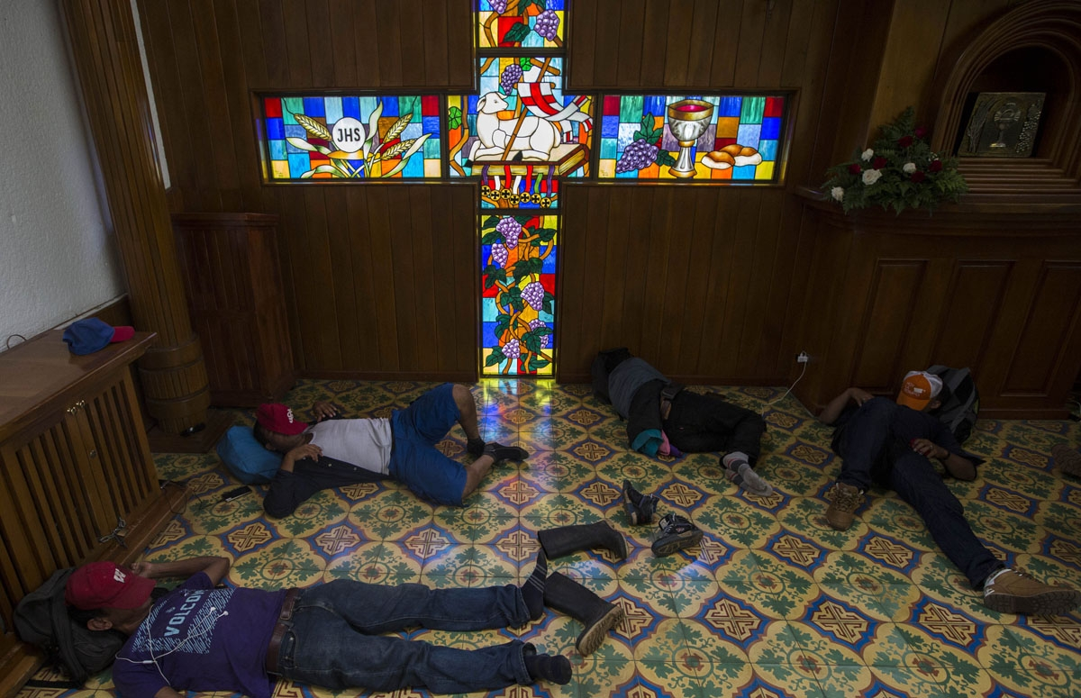 Peasants who spent the night at the Metropolitan Cathedral in Managua, where they took refuge during deadly clashes after a march marking Nicaragua's National Mother's Day, rest inside the church on May 31, 2018.