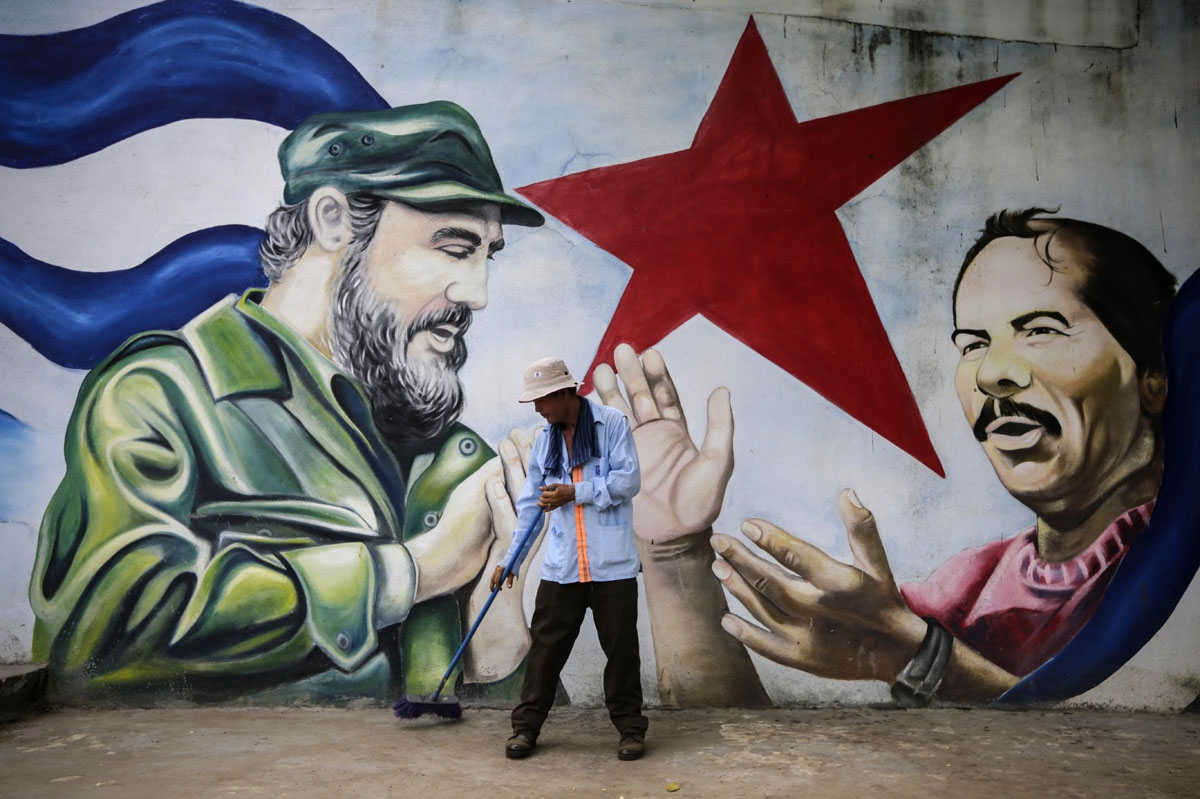 A municipal worker sweeps the floor in front of a mural depicting Cuban revolutionary leader Fidel Castro (L) and Nicaraguan President Daniel Ortega at Cuba square in Managua on November 26, 2016, the day after Castro died.