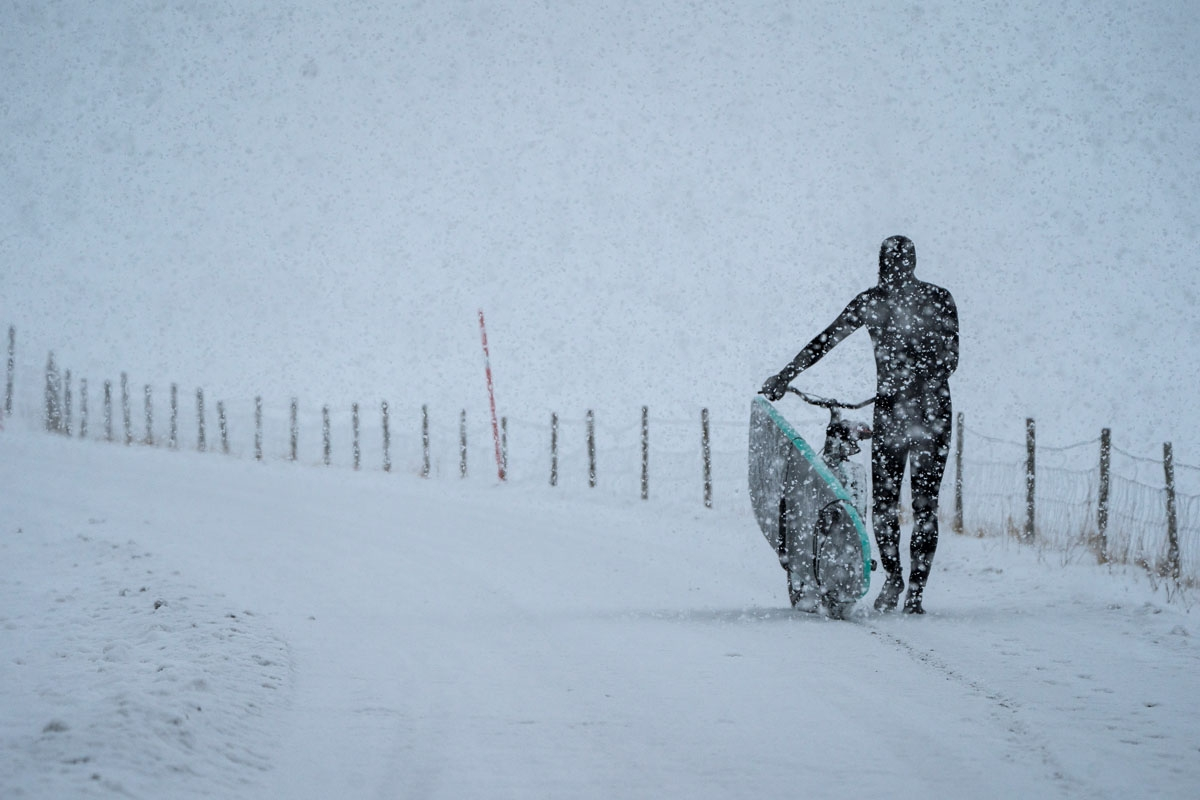 A surfer carries his surfboard on a bicycle under snowfall, on March 11, 2018, in Unstad, northern Norway, Lofoten islands, within the Arctic Circle as air temperature drops minus 13°C and water temperature above 4°C
