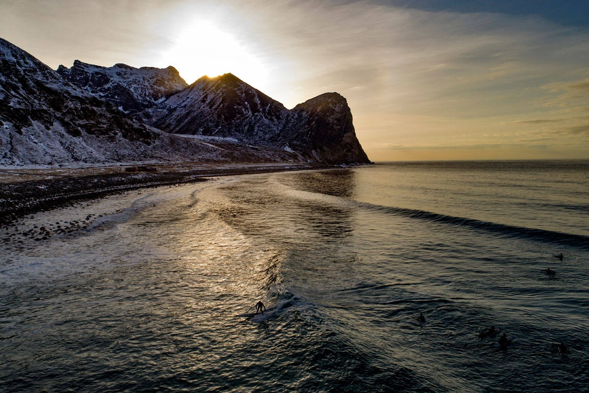 A surfer rides a wave on March 10, 2018 in Unstad, northern Norway, Lofoten islands, within the Arctic Circle as air temperature drops minus 13°C and water temperature above 4°C. / AFP PHOTO / OLIVIER MORIN