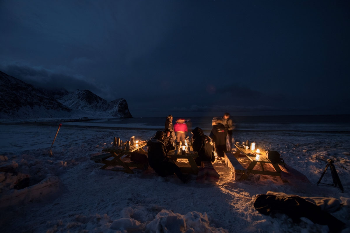 Surfers rest  in front of a camp fire after an evening of surfing in Unstad along the northern Atlantic Ocean on March 12, 2017, where the water temperatures is at five degrees centigrade and the air temperature is at minus two degrees centigrade.