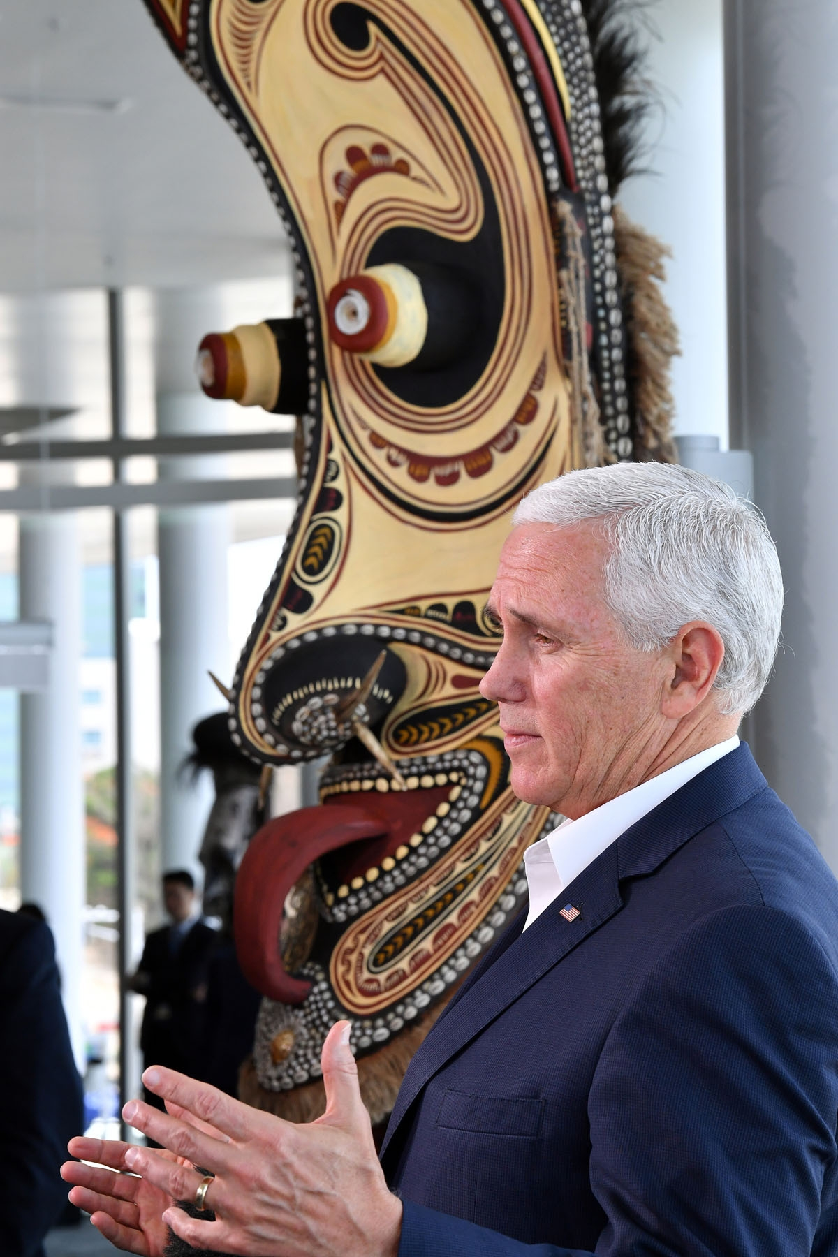 US Vice President Mike Pence speaks to the media while standing next to a traditional mask display, at the end of meetings at the Asia-Pacific Economic Cooperation (APEC) Summit in Port Moresby on November 18, 2018. (