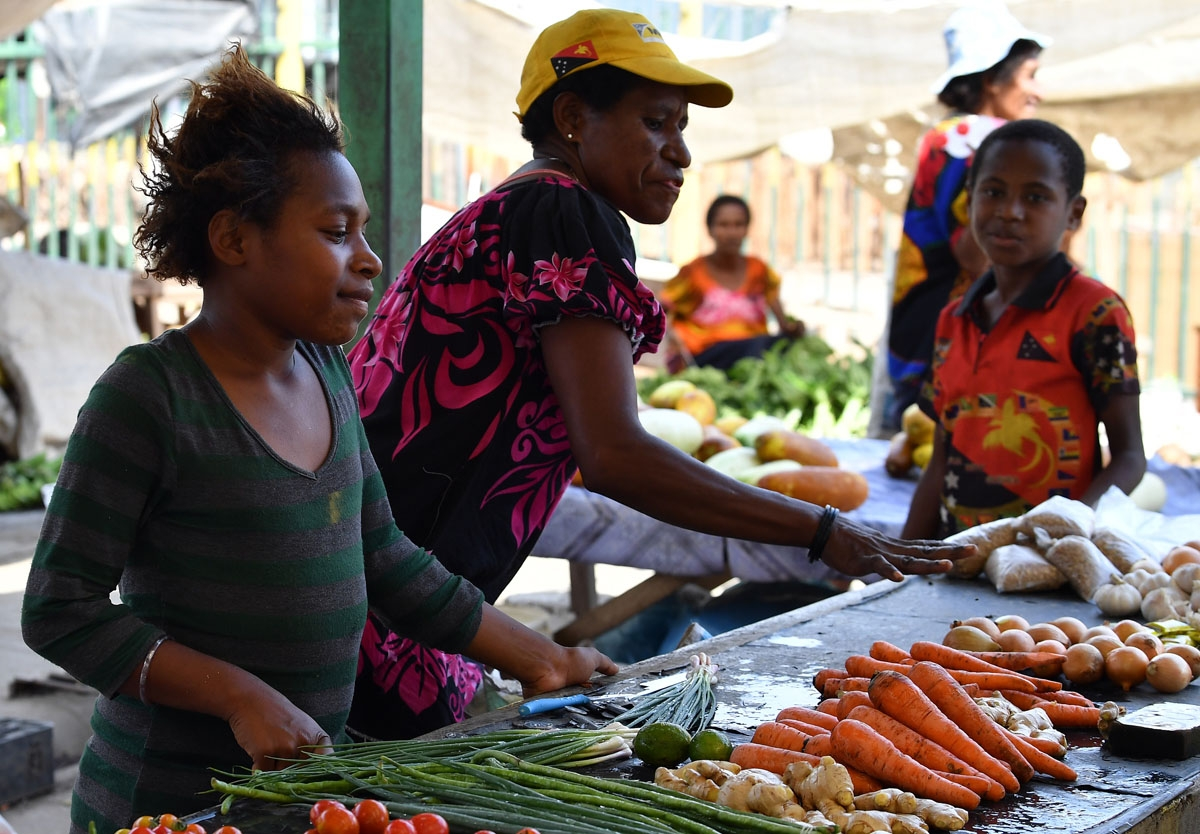 Vendors sell vegetables at a women's only makeshift market on the outskirts of Port Moresby on November 19, 2018, one day after the Asia-Pacific Economic Cooperation (APEC) Summit.