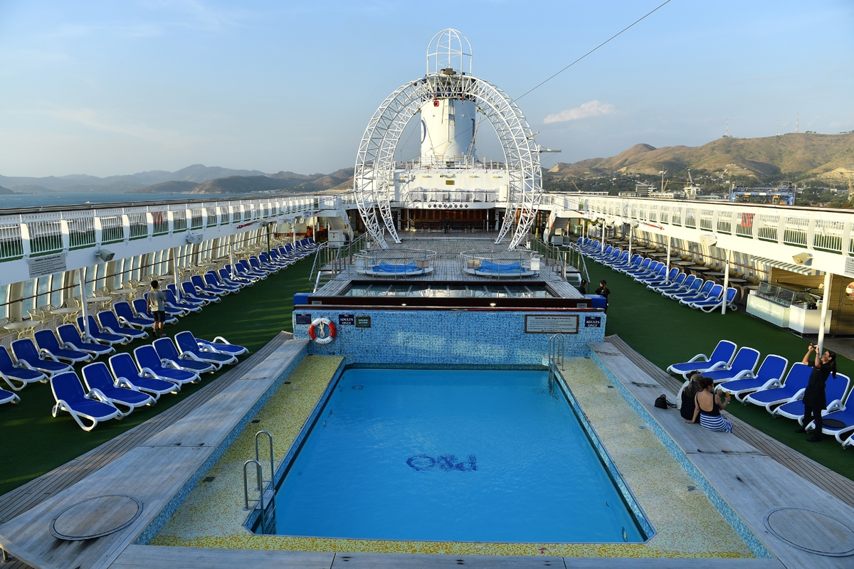 This picture taken on November 13, 2018 shows people on the deck of the cruise ship Pacific Jewels, which will accommodate delegates and journalists at this year's Asia-Pacific Economic Cooperation (APEC) Summit, in Port Moresby.