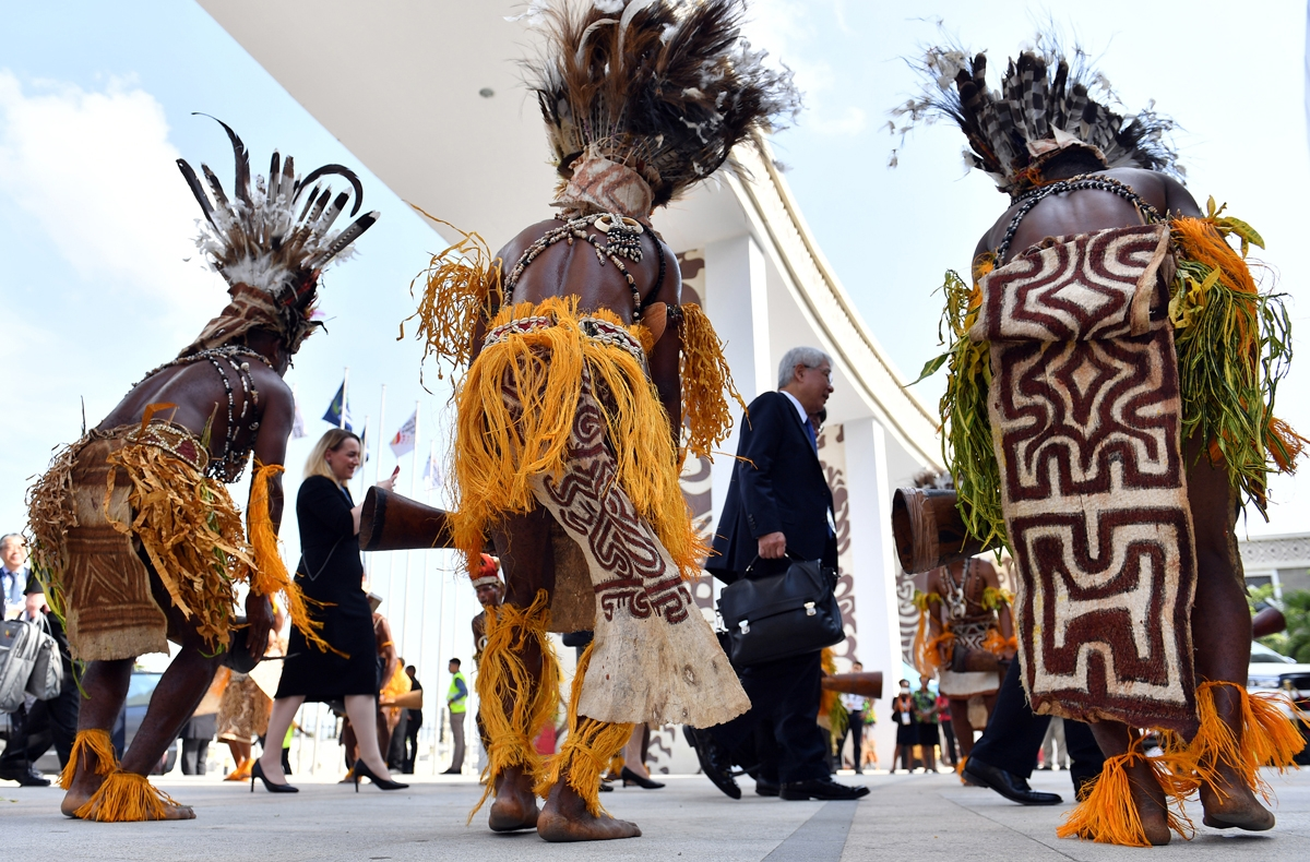 Performers in traditional costumes and headdress welcome delegates and ministers to the international convention centre for the 30th Asia-Pacific Economic Cooperation (APEC) ministerial meeting in Port Moresby on November 15, 2018.