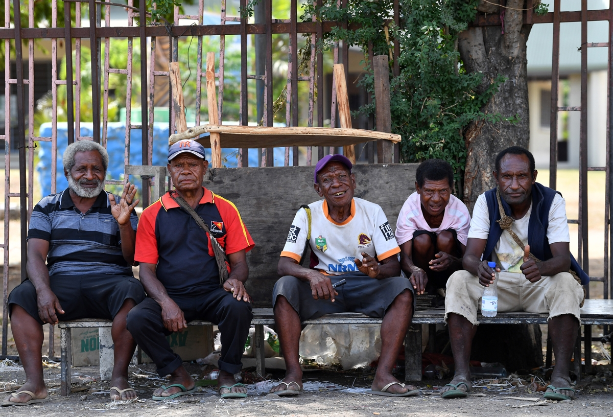 Papuan villagers sit outside a women's only makeshift market on the outskirts of Port Moresby on November 19, 2018, one day after the Asia-Pacific Economic Cooperation (APEC) Summit.