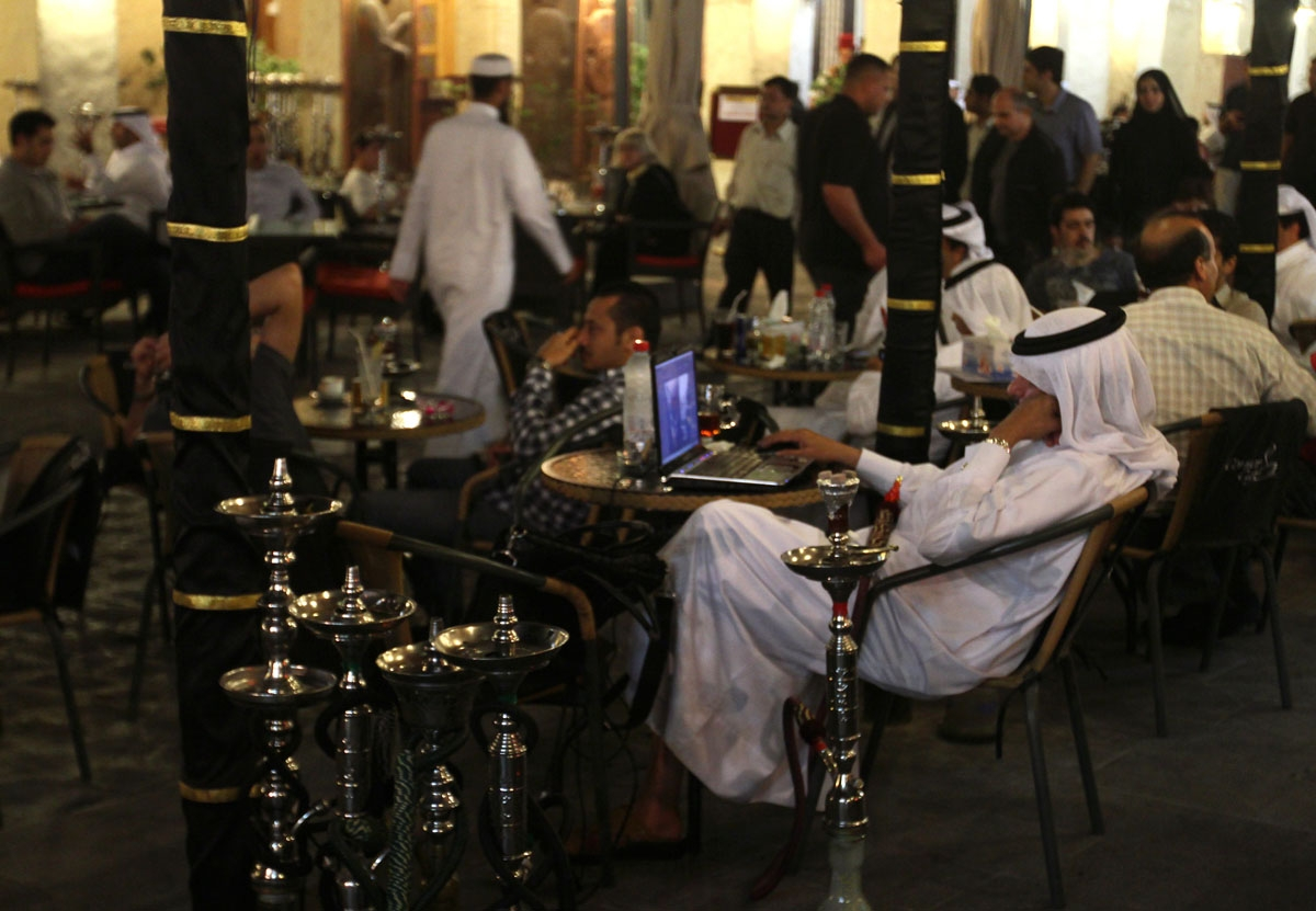 A Qatari man works on his laptop at a cafe at the Souq Waqif market in the old city of Doha late on March 10, 2010.