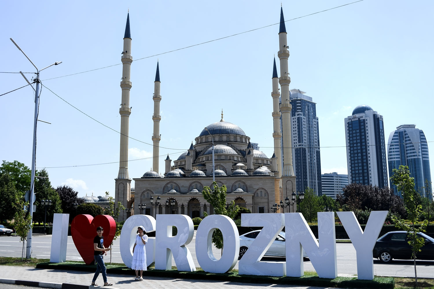 Young people take a photo in front of the Heart of Chechnya - Akhmad Kadyrov Mosque and large letters reading 'I love Grozny' in central Grozny on July 26, 2017.