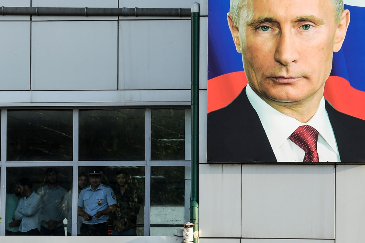 People look out of a window at Grozny Airport adorned with a portrait of Russian President Vladimir Putin in Grozny, on July 24, 2017.