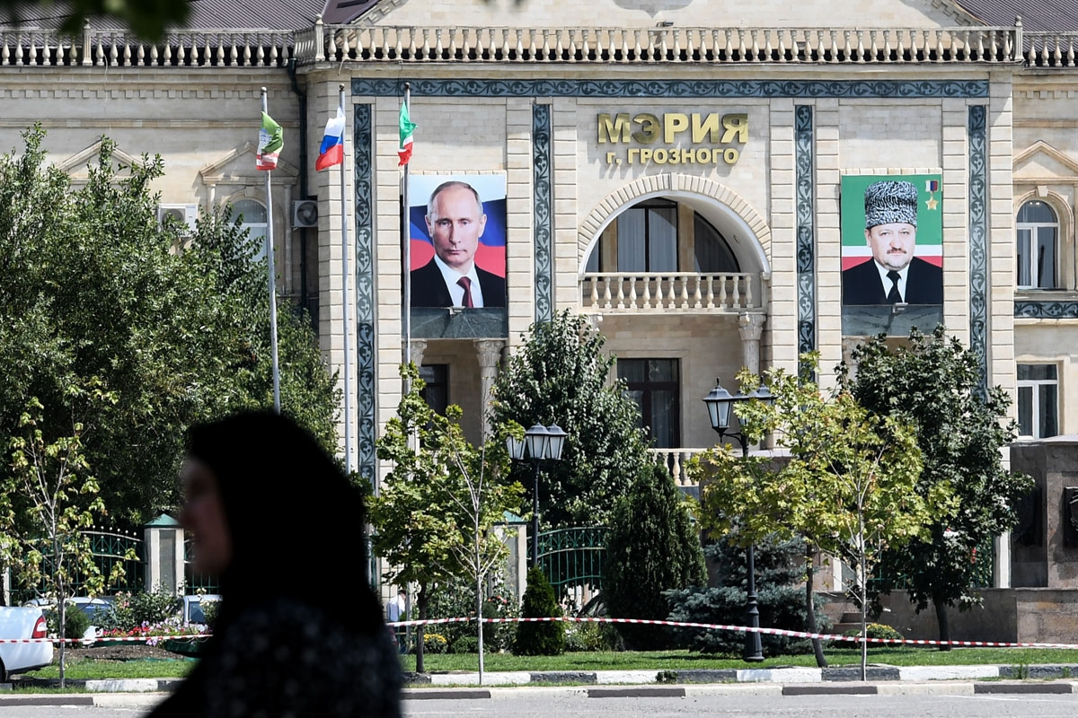 A woman walks on an avenue named after Russian President Vladimir Putin in front of the Grozny city administration's building displaying portraits of Russian President Vladimir Putin (L) and Akhmad Kadyrov (R), former Chechen Republic's president and fath