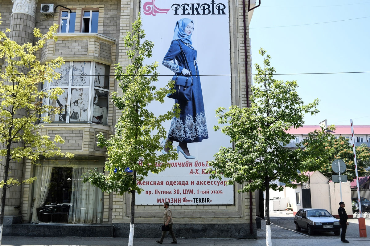 A man walks past a banner showing a woman dressed in Islamic clothes on an avenue named after Russian President Vladimir Putin in central Grozny on July 26, 2017.
