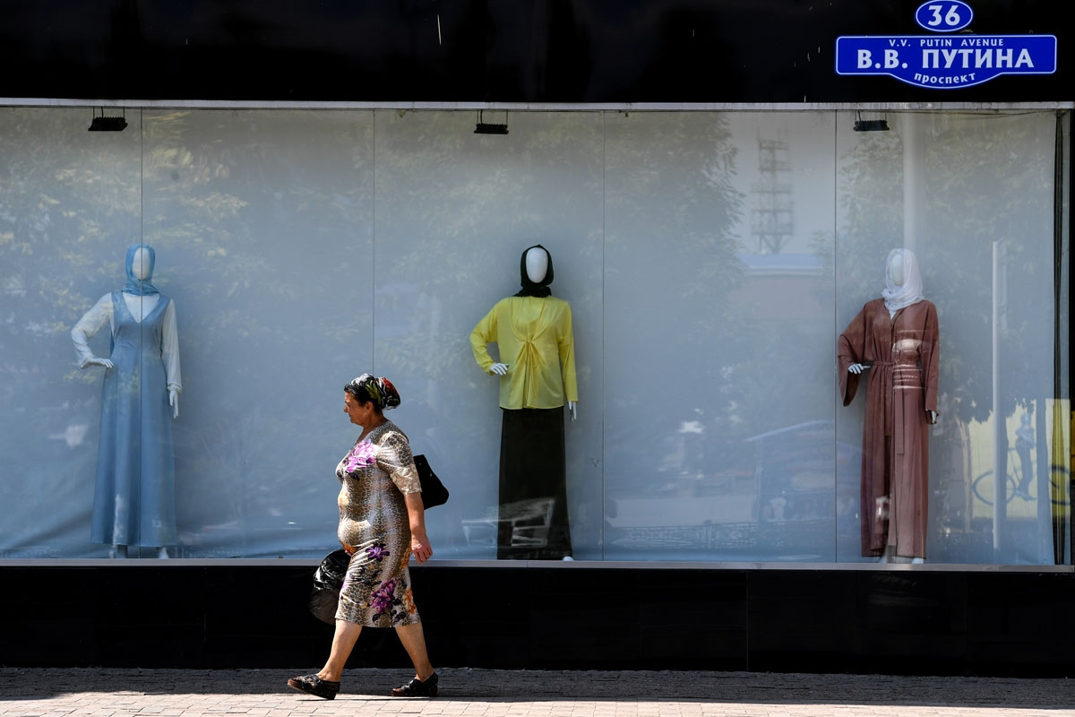 A woman walks past a shop selling Islamic clothes for women on an avenue named after Russian President Vladimir Putin in central Grozny on July 26, 2017.