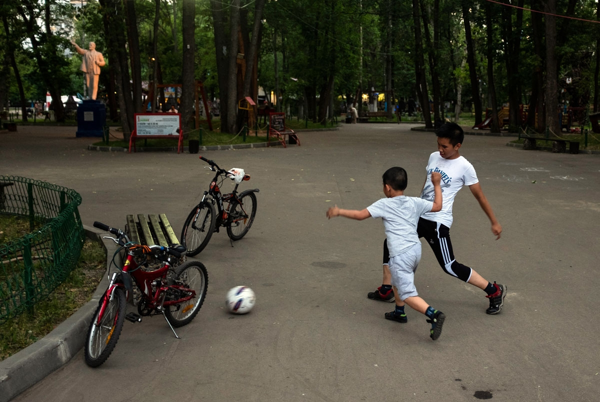 Boys play football next to a statue of Vladimir Lenin, the founder of the Soviet Union, in a park in Nizhny Novgorod on July 1, 2018. /