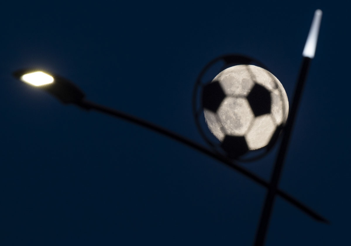 The moon shines behind a lamp post shaped as a soccer ball next to the Nizhny Novgorod Stadium in Nizhny Novgorod, on June 26, 2018 during the Russia 2018 World Cup tournament.