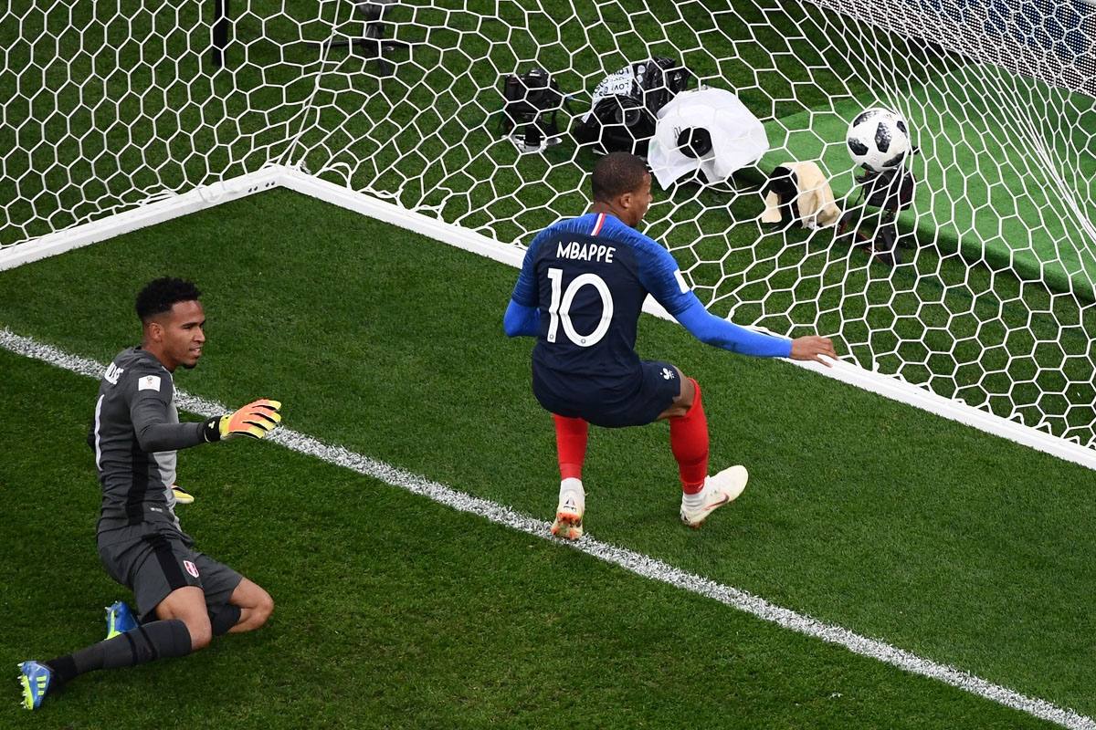 ance's forward Kylian Mbappe (R) scores a goal during the Russia 2018 World Cup Group C football match between France and Peru at the Ekaterinburg Arena in Ekaterinburg on June 21, 2018. / A