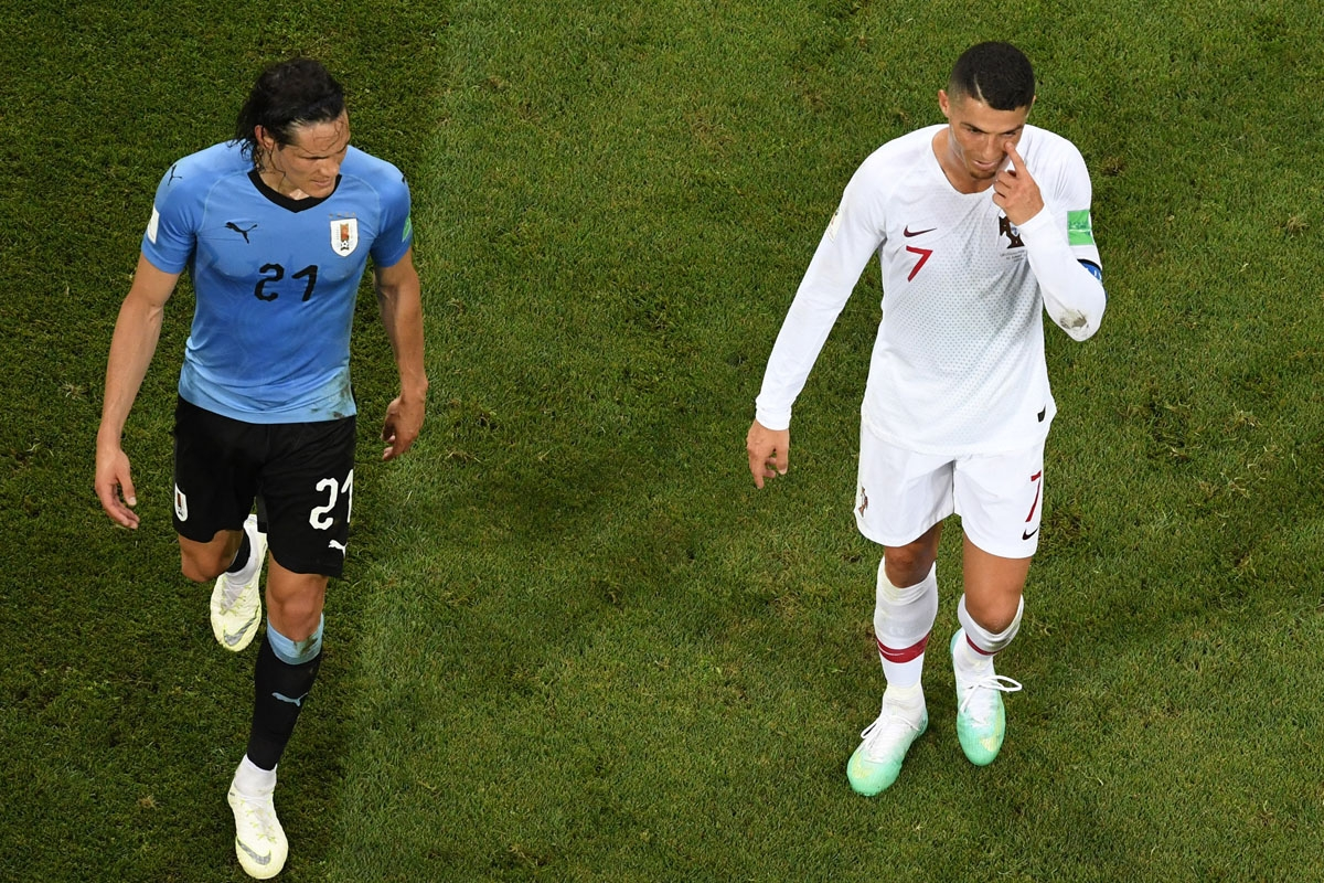 Portugal's forward Cristiano Ronaldo (R) gestures next to Uruguay's forward Edinson Cavani during the Russia 2018 World Cup round of 16 football match between Uruguay and Portugal at the Fisht Stadium in Sochi on June 30, 2018. /