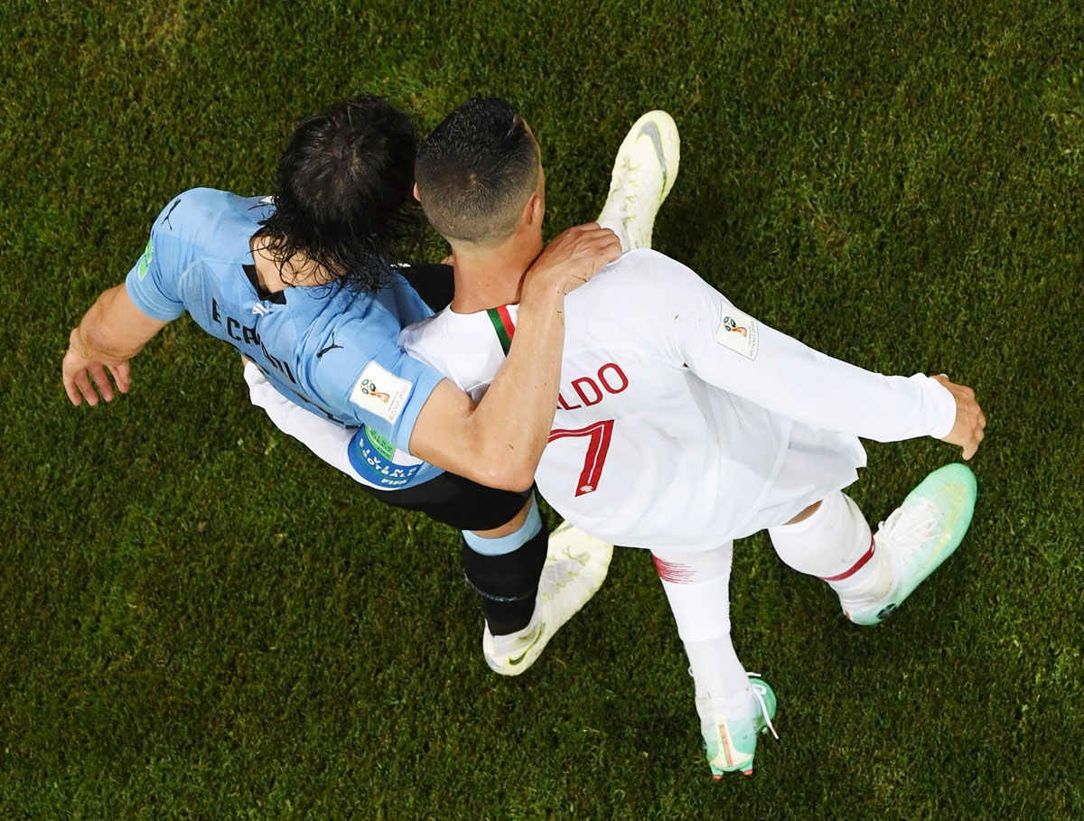 Portugal's forward Cristiano Ronaldo (R) hugs Uruguay's forward Edinson Cavani during the Russia 2018 World Cup round of 16 football match between Uruguay and Portugal at the Fisht Stadium in Sochi on June 30, 2018. /