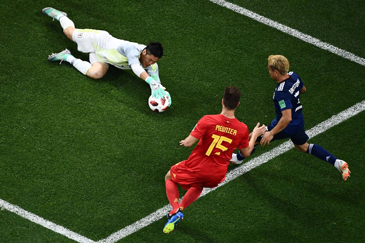 Japan's goalkeeper Eiji Kawashima (L) stops a shot on goal by Belgium's defender Thomas Meunier (C) during the Russia 2018 World Cup round of 16 football match between Belgium and Japan at the Rostov Arena in Rostov-On-Don on July 2, 2018.