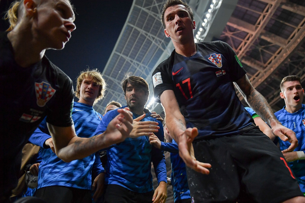 Croatia's forward Mario Mandzukic (C) offers to help AFP photographer Yuri Cortez after he fell on him with teammates while celebrating their second goal during the Russia 2018 World Cup semi-final football match between Croatia and England at the Luzhnik