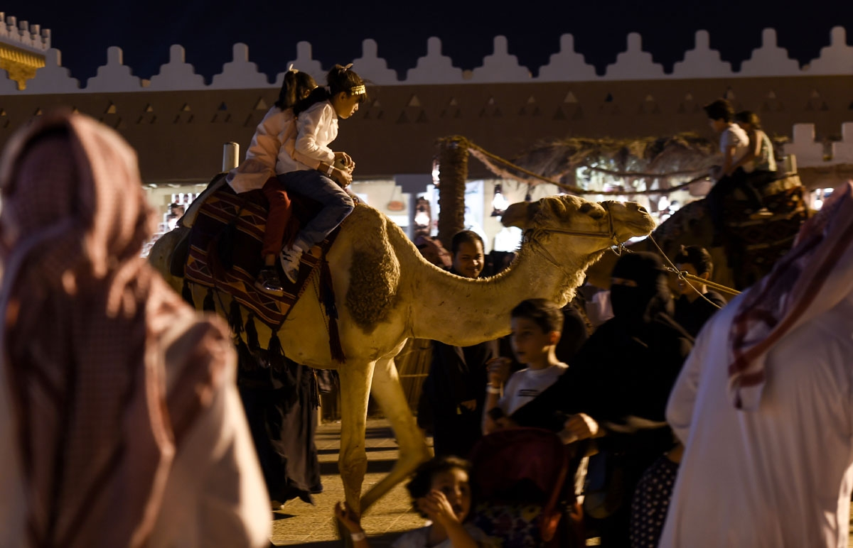 Saudi children ride a camel at Al-Qasim pavilion, during the 32nd Janadriyah Culture and Heritage Festival, held on the outskirts of the capital Riyadh on February 17, 2018. / AFP PHOTO / Fayez Nureldine