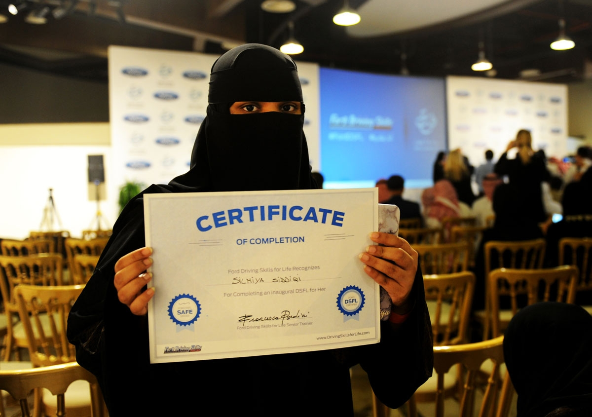 A Saudi woman poses for a photo with a certificate after completing a driving course in Jeddah on March 7, 2018.
