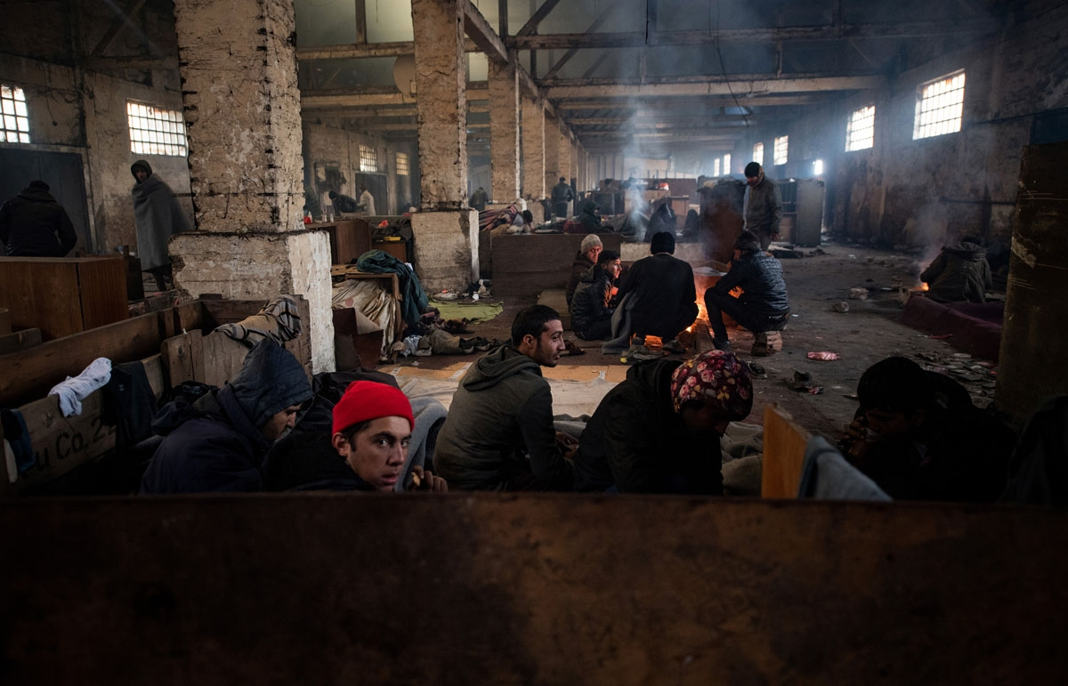 Migrants rest in a makeshift shelter in an abandoned warehouse in Belgrade on November 16, 2016.
