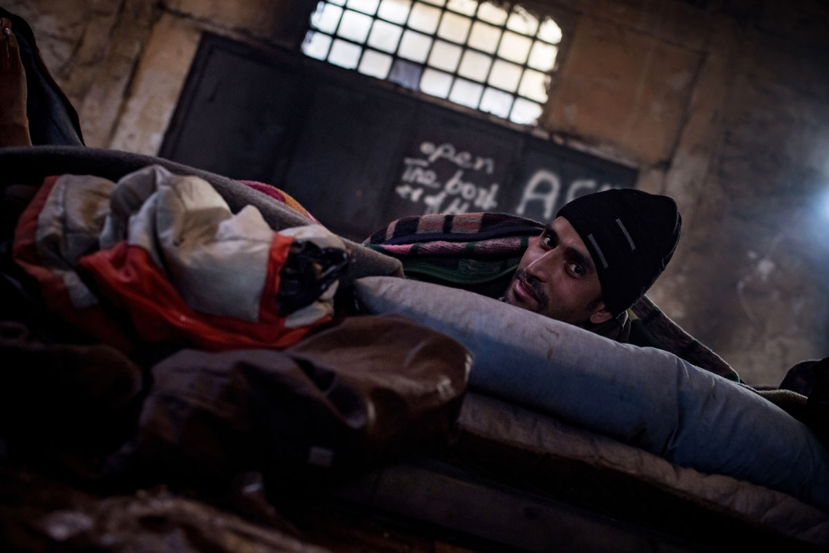 A migrant sits in a makeshift shelter at an abandoned warehouse in Belgrade on December 8, 2016.