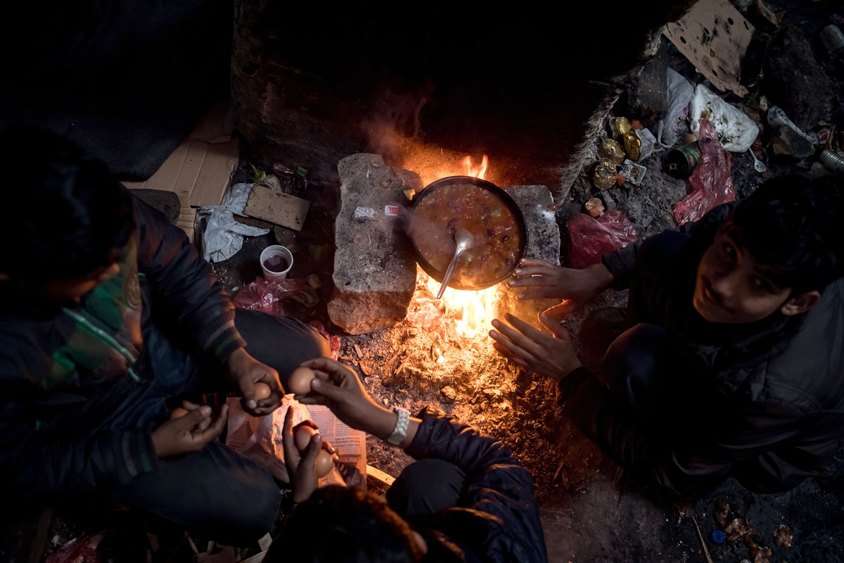 Migrants prepare a meal at a makeshift shelter at an abandoned warehouse in Belgrade on December 8, 2016.
